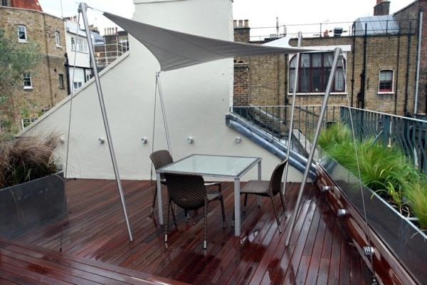 Tenda da sole bianca indipendente sopra la zona salotto della terrazza sul tetto